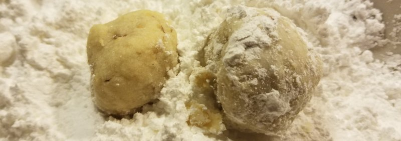 After your cookies have cooled on a wire rack for 5 minutes you're ready to roll them in powdered sugar.